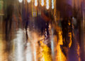Abstract background of people figures, city street in rain, orange-brown tones. Intentional motion blur. Bright Royalty Free Stock Photo