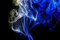 Abstract blue and yellow smoke from the aromatic sticks. Royalty Free Stock Photo
