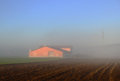 Abstract blur feding red barn on farm with blue sky in winter Royalty Free Stock Photo