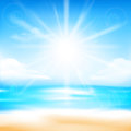 Abstract blur sand beach and blue sky background with sunlight