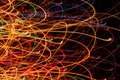 Abstract bright multicolored glowing lines and curves on black background against a Royalty Free Stock Image