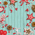 Abstract christmas background, dry branches with red berries and small scandinavian styled decorations lying on wooden Royalty Free Stock Photo