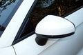 Abstract closeup side view of rear view mirror and vehicle Stock Photo