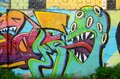 Abstract colorful fragment of graffiti paintings on old brick wall with scary octopus face. Street art composition with parts of Royalty Free Stock Photo