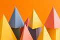 Abstract colorful geometrical background. Three-dimensional prism pyramid objects on orange paper. Yellow blue pink Royalty Free Stock Photo