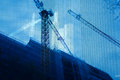 Abstract construction background multy layered in blue tone with cranes and tall skyscraper building being rised Stock Photography