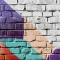 Abstract detail of brick wall with fragment of colorful graffiti. Urban Art close-up. With place for your text, for Royalty Free Stock Photo