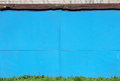 Abstract detailed blue metal wall background texture of sheet  painted with  paint, grass, sun visor  the roofing material and bri Royalty Free Stock Photo