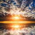 Abstract dramatic sunset at the sea ocean sun and clouds reflection in water Royalty Free Stock Photography