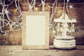 Abstract image of old vintage white carousel horses with garland gold lights and blank frame on wooden table. retro filtered image