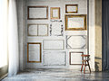 Abstract interior of assorted classic empty picture frames against a white brick wall with rustic hardwood floors Royalty Free Stock Photo