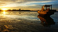 Abstract landscape of sea boat reflect when sunset tide going out sun go down sunbeam shine on wooden fishing that relfect on Royalty Free Stock Photos