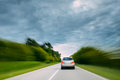 Abstract Natural Blurred Background Of Luxury Suv Car In Fast Motion On Road At Summer. Cloudy Sky Above Asphalt