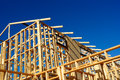 Abstract of new home construction site framing residential house against a blue sky Stock Image