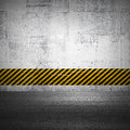 Abstract parking interior fragment with asphalt ground and striped yellow and black pattern on the concrete wall Royalty Free Stock Image