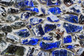Abstract pattern of blue glass stones in concrete gray wall. Royalty Free Stock Photo