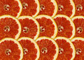 Abstract red background with citrus fruit of grapefruit slices close up Stock Photo