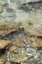 Abstract sea background with water covering stones and pebbles. Vertical orientation Royalty Free Stock Photo