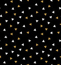 Abstract seamless pattern with triangles in gold and white on the dark gray background.