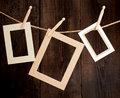 Abstract sign close up of three photo frames and clothes pegs on a rope over a wooden background Royalty Free Stock Images