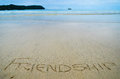 Abstract sign of word friendship written on a sand beach background