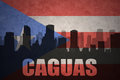 Abstract silhouette of the city with text Caguas at the vintage puerto rican flag