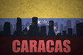 Abstract silhouette of the city with text Caracas at the vintage venezuelan flag