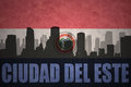 Abstract silhouette of the city with text Ciudad del Este at the vintage paraguayan flag