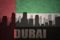 Abstract silhouette of the city with text Dubai at the vintage united arab emirates flag