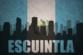 Abstract silhouette of the city with text Escuintla at the vintage guatemalan flag