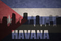 Abstract silhouette of the city with text Havana at the vintage cuban flag