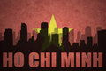 Abstract silhouette of the city with text Ho Chi Minh at the vintage vietnamese flag