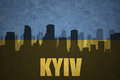 Abstract silhouette of the city with text Kyiv at the vintage ukrainian flag