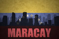 Abstract silhouette of the city with text Maracay at the vintage venezuelan flag