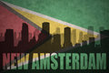 Abstract silhouette of the city with text New Amsterdam at the vintage guyana flag