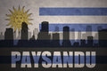 Abstract silhouette of the city with text Paysandu at the vintage uruguayan flag