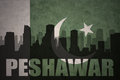 Abstract silhouette of the city with text Peshawar at the vintage pakistan flag