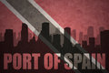 Abstract silhouette of the city with text Port of Spain at the vintage trinidad and tobago flag