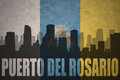 Abstract silhouette of the city with text Puerto del Rosario at the vintage canary islands flag