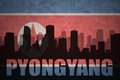 Abstract silhouette of the city with text Pyongyang at the vintage north korea flag