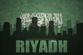 Abstract silhouette of the city with text Riyadh at the vintage saudi arabia flag