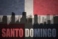 Abstract silhouette of the city with text Santo Domingo at the vintage dominican republic flag