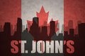 Abstract silhouette of the city with text St. John`s at the vintage canadian flag