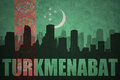 Abstract silhouette of the city with text Turkmenabat at the vintage turkmenistan flag