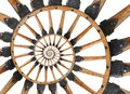 Abstract spiral wooden wagon cannon wheel black metal brackets rivets. Wheel wooden spokes fractal background. Horse vehicle wheel Royalty Free Stock Photo
