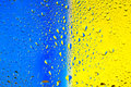 Abstract texture. Water drops on glass with blue and yellow background