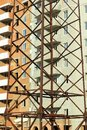 Abstract vertical industrial background of brick multistory building under construction behind close up power lines pylon tower Royalty Free Stock Photo