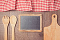 Abstract wooden background with red checked tablecloth, chalkboard and kitchen utensils. View from above Royalty Free Stock Photo