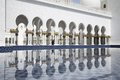 Abu dhabi grand moss white arcades and water surface reflection gold ornamented columns Stock Images