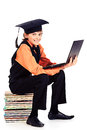 Academic boy happy schoolboy in hat sitting on a stack of books and holding a laptop isolated over white Royalty Free Stock Image